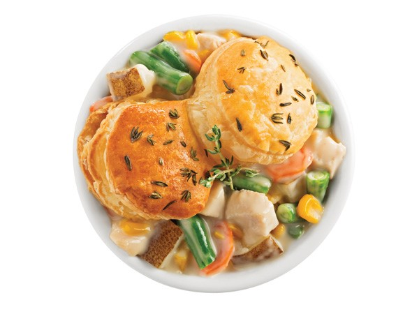 Bowl of chicken pot pie topped with two biscuits