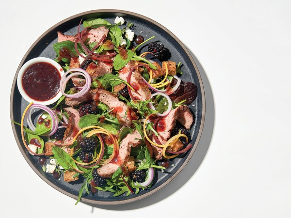 Salad topped with blackberries, greens, steak, and onions