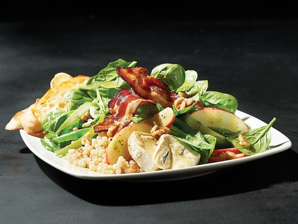 Dish filled with couscous, spinach, asparagus, green beans, apple slices, bacon, walnuts and blue cheese