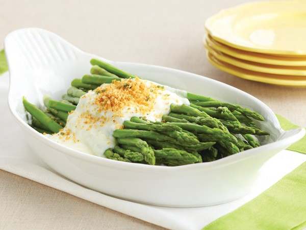 White dish of steamed asparagus topped with cream sauce and breadcrumbs