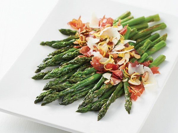 Platter of asparagus topped with crispy prosciutto, almonds, Parmigiano-Reggiano cheese and lemon zest
