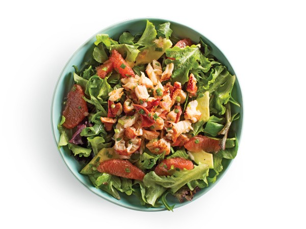 Shredded lobster and citrus wedges on top of salad greens