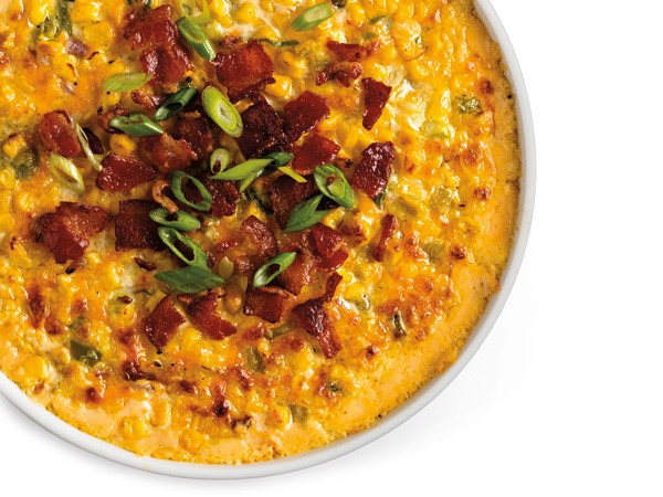 Dish filled with cheesy corn casserole and topped with crumbled bacon bits and chopped green onions