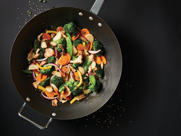 Skillet filled with vegetable stir-fry topped with sesame seeds