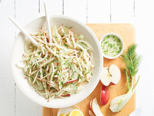 Small bowl of crunchy apple and fennel slaw next to cutting board with apple slices, fennel and dressing