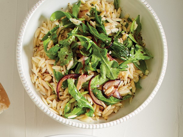 Bowl of orzo, arugula and red onions