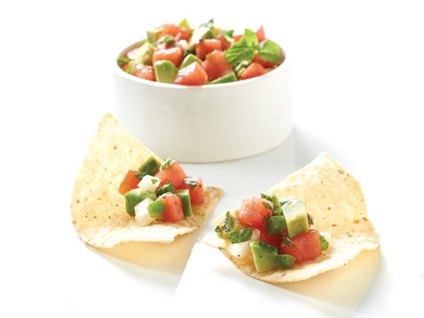 Tortilla chip filled with avocado melon salsa