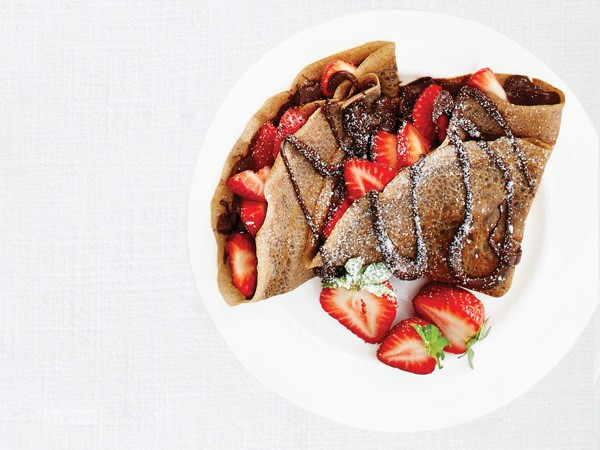 Crepe filled with hazelnut spread and topped with strawberries, chocolate-hazelnut drizzle and powdered sugar