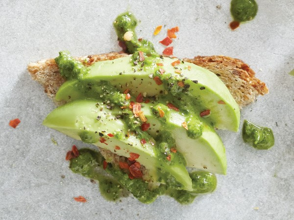 Whole-grain bread slice topped with avocado, arugula mixture and red pepper flakes