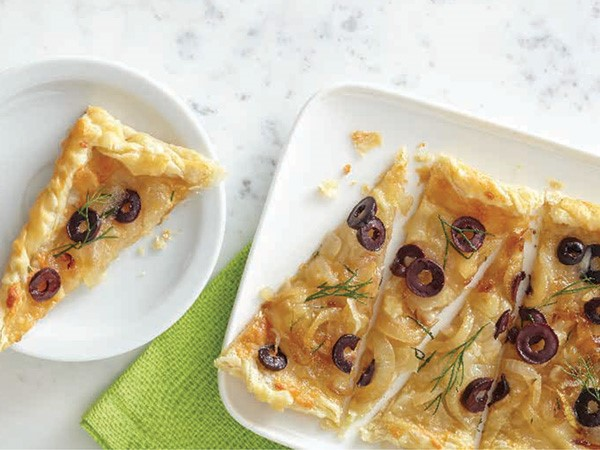 Carmelized-onion tart slices topped with fresh dill and kalamata olives