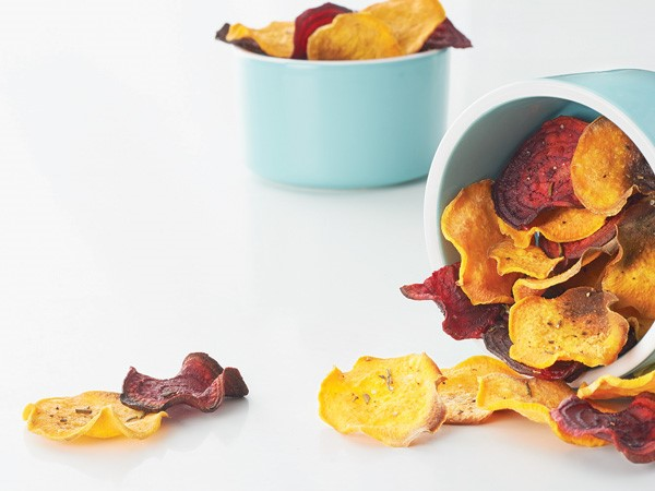 Sweet potato and beet chips spilling out of blue containers