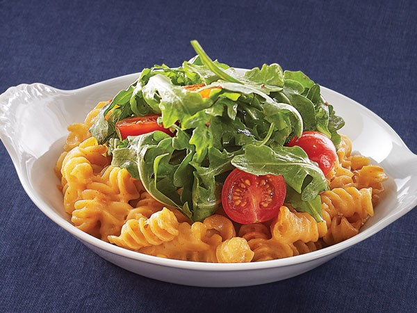 Mac and cheese topped with tomatoes and fresh arugula