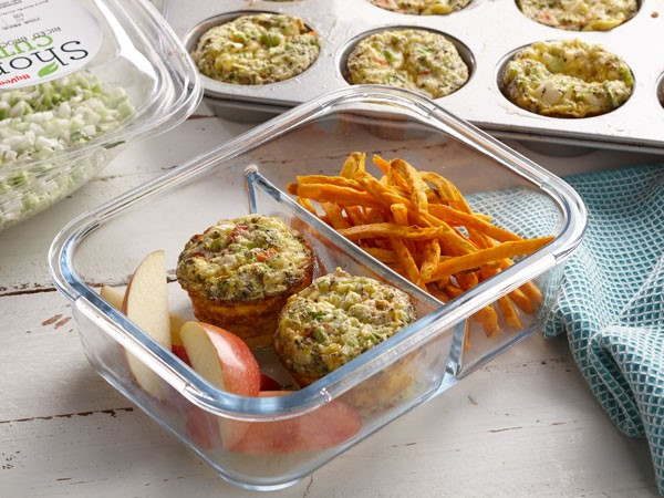 Plastic container with two baked egg muffins, apple slices and sweet potato fries