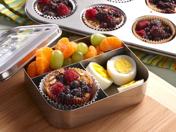 Aluminum container with compartments filled with a baked oatmeal cup, hard boiled eggs and fruit