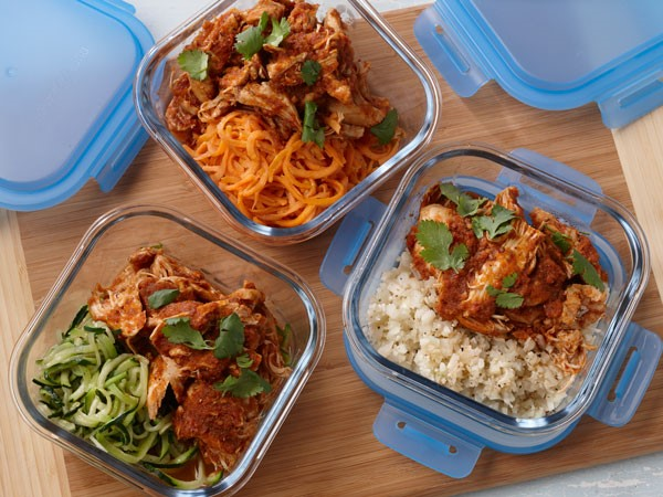 Glass containers filled with chicken tinga and sides of rice, zucchini or carrots