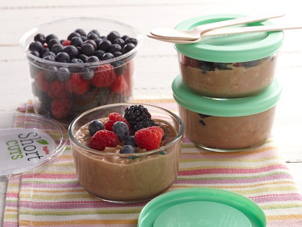 Glass containers of chocolate cauliflower rice oatmeal topped with fresh raspberries, blackberries and blueberries