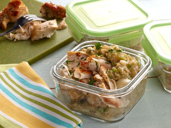 Mashed veggies topped with shredded chicken in glass container