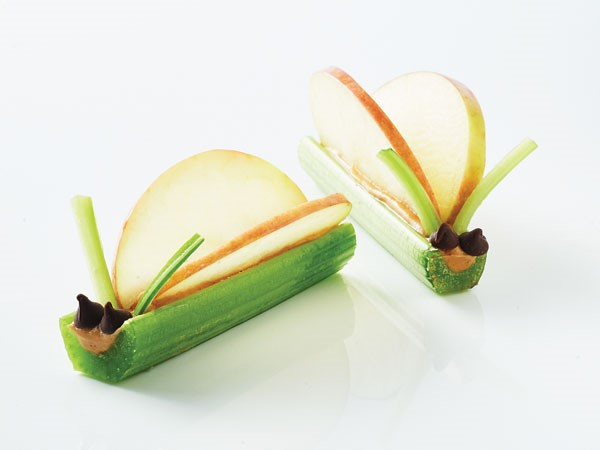 Celery sticks filled with peanut butter and topped with two chocolate chips, two apple slices and two thin strips of celery to form a celery critter