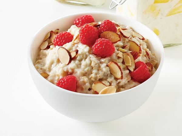 Oatmeal in white bowl topped with sliced almonds and raspberries