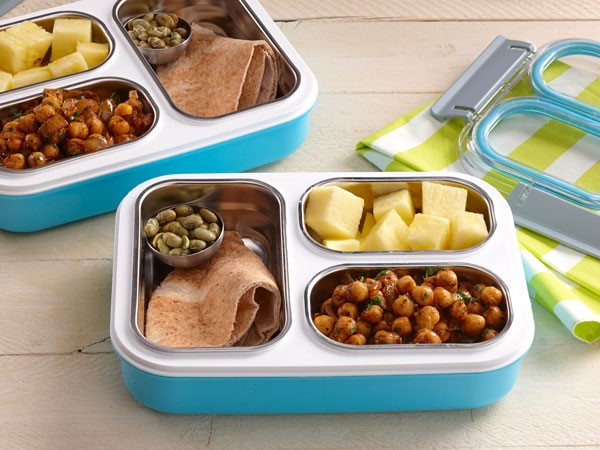 Bento box filled with pitas, edamame, pineapple, and garam masala chickpeas