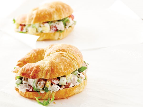 Chicken waldorf salad sandwiched between a sliced croissant
