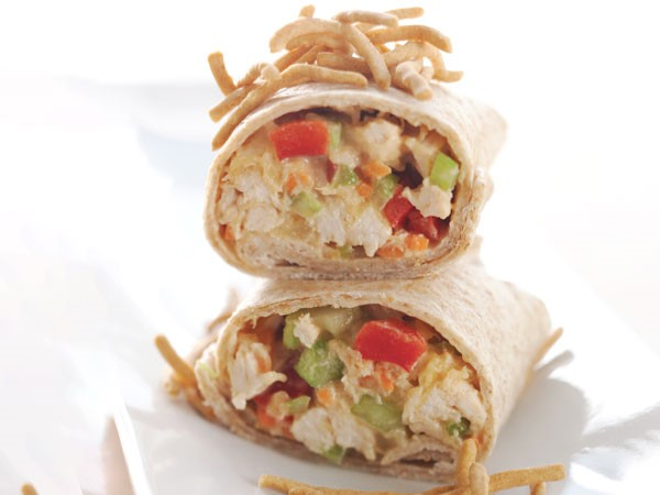 Asian chicken salad wraps stacked on parchment paper