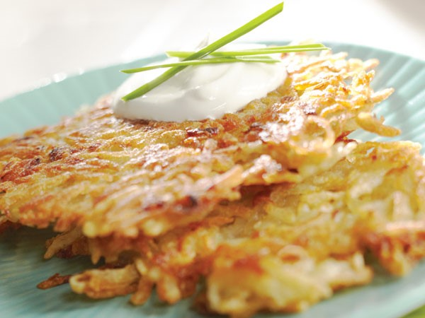 Crunchy potato pancakes garnished with sour cream and fresh chives