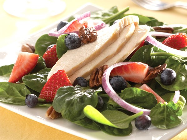 Plate of spinach topped with strawberries, blueberries, chicken slices, red onion, pecans and vinaigrette