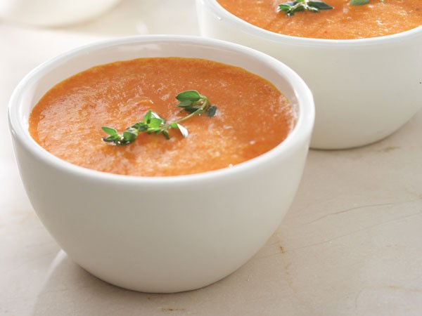 White bowl filled with creamy roasted tomato soup