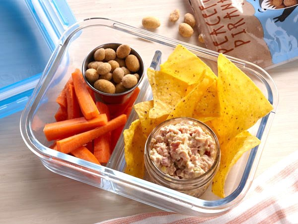 Ham salad in bento box with chips, nuts, and carrot sticks