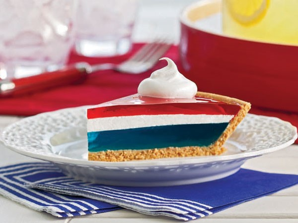 Red, white, and blue jello pie with graham cracker crust on white plate