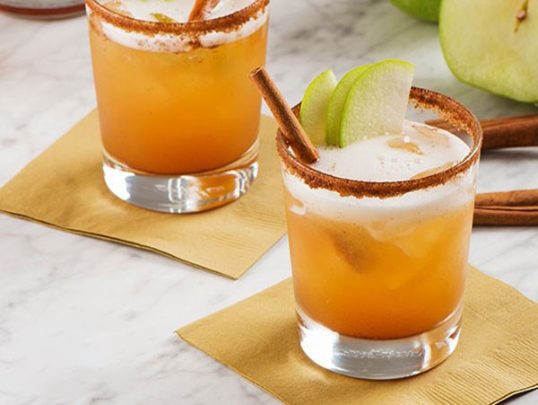 Cocktail made with beer in a cinnamon-rimmed glass and apple garnish
