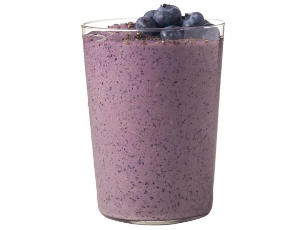 Glass of blueberry madness protein shake topped with fresh blueberries
