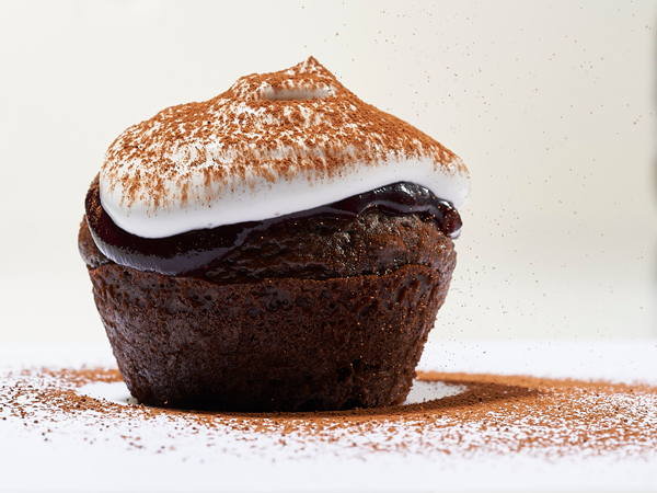 Chocolate cupcake topped with white frosting and cocoa powder