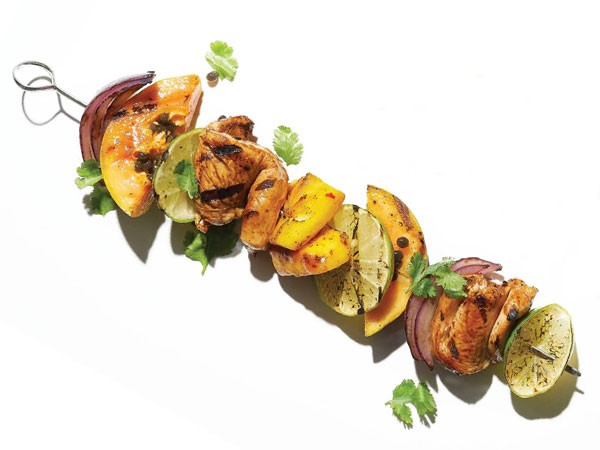 Grilled chicken, papaya, mango, and red onion on a metal skewer