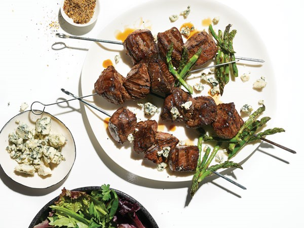 Beef skewered with asparagus on white plate