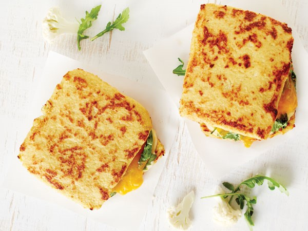 Two cauliflower grilled cheese sandwiches on white background