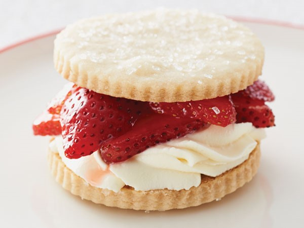 Shortbread cookies sandwiching frosting and fresh strawberry slices