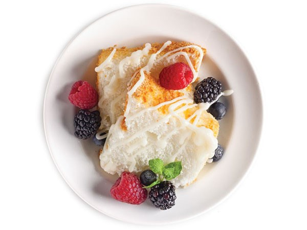 Plate of angel food cake topped with drizzled icing and fresh berries