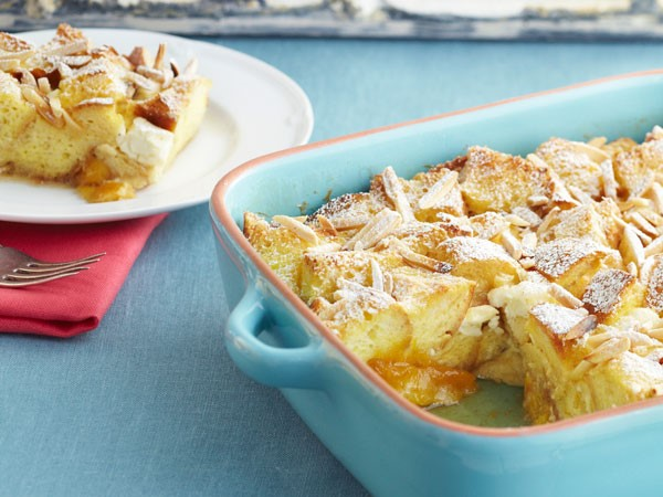 Peaches and cream French toast in teal casserole dish with slice on white plate