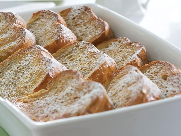 Casserole dish of baked french toast topped with powdered sugar
