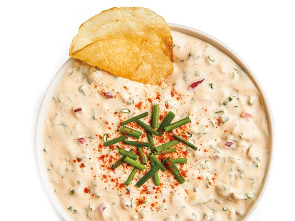 Party dip in white bowl topped with chopped chives and kettle chip