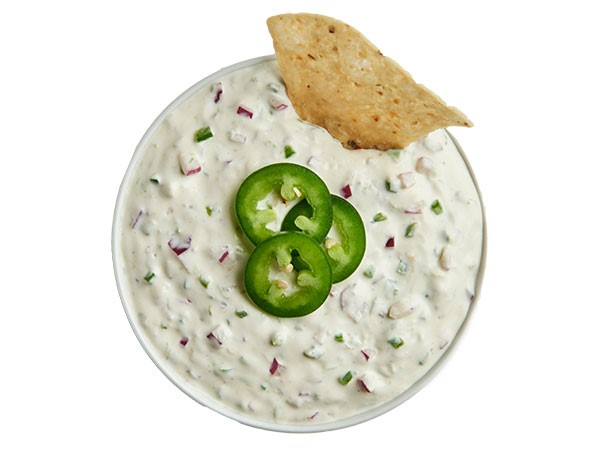 Cilantro lime dip garnished with fresh jalapeno slices and chip