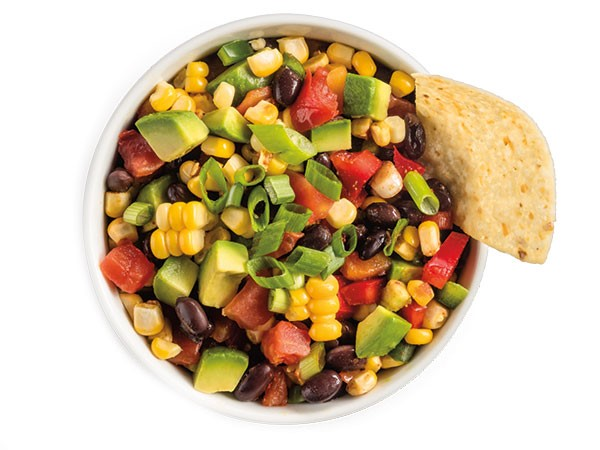Chunky avocado salsa with corn, black beans, and tomatoes with chip.