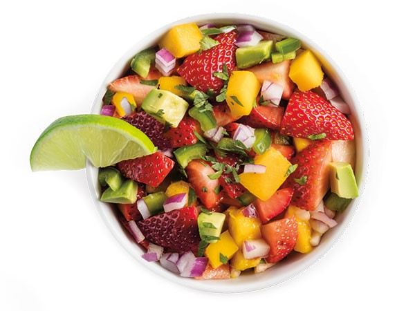 Strawberry avocado pico de gallo with fresh fruit and veggies in a white bowl with lime wedge