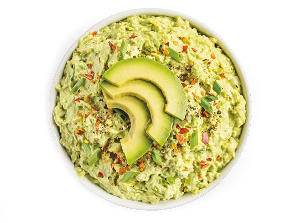 Creamy avocado dip garnished with green onions, avocado slices, and red pepper flakes