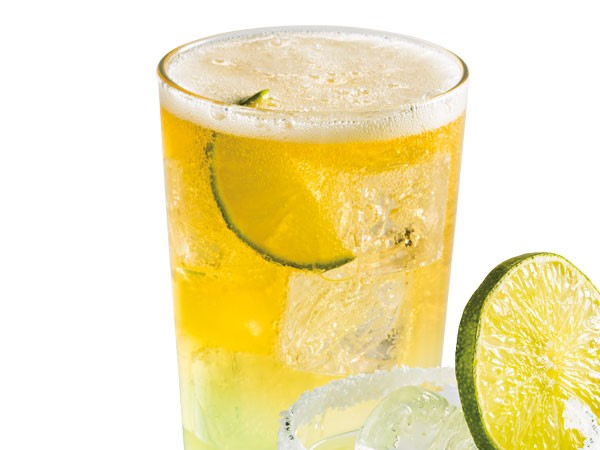 Glass filled with beer-rita, ice and lime slices