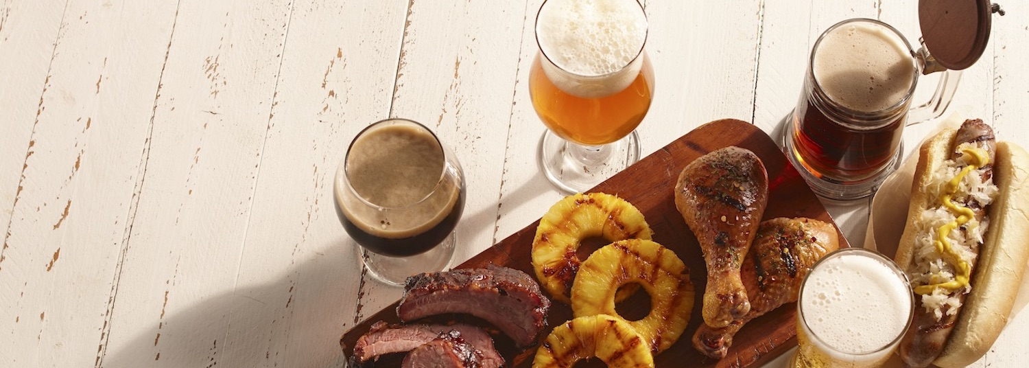 White wooden background with beer, brats, grilled pineapple, chicken, and ribs