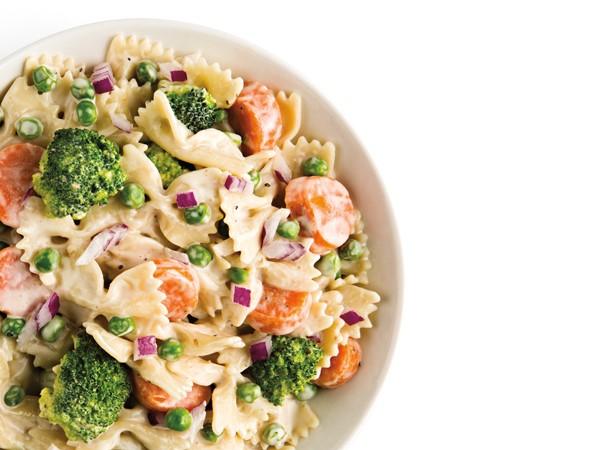 Broccoli pasta salad with fresh veggies in white bowl