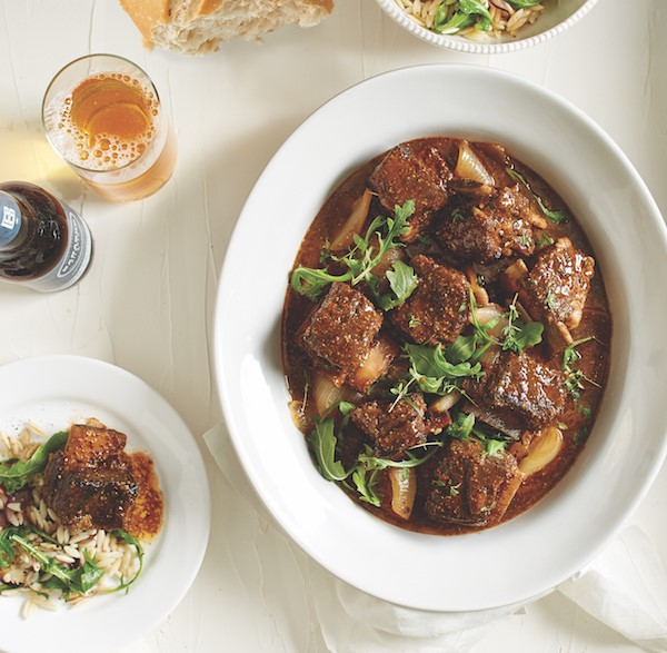 Bowl of beer-braised short ribs with onions and arugula leaves